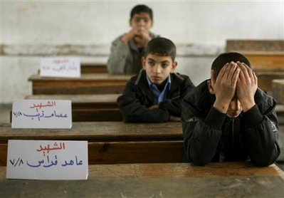 Palestinian boy Mohammed Kutkut, 14, right, covers his face as he sits next to the name sign of his killed friend Ahed Qaddas in the Fakhoura boys school in Jebaliya, northern Gaza strip, Saturday, Jan. 24, 2009. Three friends of his class where killed when the Israeli army shelled Jebaliya in the past weeks. Tens of thousands of children have flocked back to schools throughout the Gaza Strip, days after Israel ended its fierce military operation against the territory's rulers.  (AP Photo/Anja Niedringhaus)