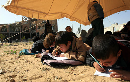 Palestinian children attend their first day of class in over a month inside a tent erected beside the ruins of their destroyed school in the southern Gaza Strip town of Rafah. (Wissam Nassar, Maan Images)