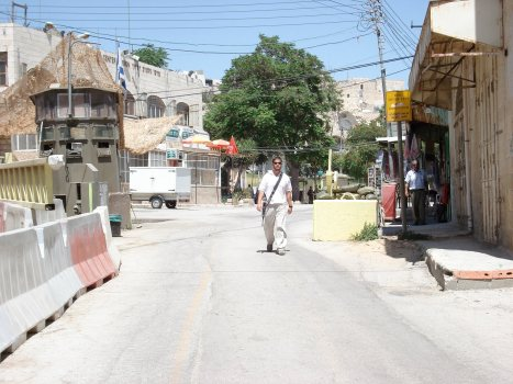 israeli terrorist colonist with his m16 walking the streets of khalil