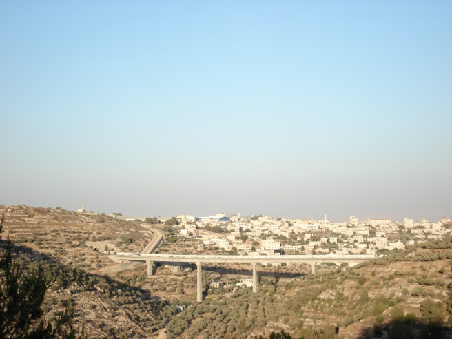 jewish only road cutting through beit jala with apartheid wall & sniper towers in distance